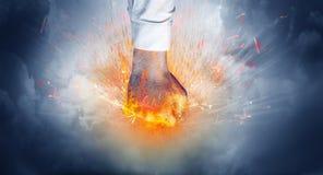 La mano golpea intenso y hace el fuego fotografía de archivo libre de regalías