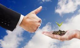 La mano gradisce e mano con il seme e monete sopra il fondo della nuvola Immagini Stock