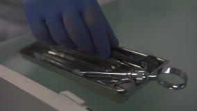La mano in guanti medici prende a dantist lo strumento chirurgico dalla scatola in clinica durante le procedure stomatologic stock footage