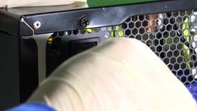 La mano in guanti protettivi estrae il bottone e disinserisce il cavo elettrico dal PC stock footage