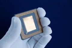La mano in guanto bianco tiene un chip di computer immagine stock