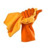 La mano in guanto di gomma arancio tiene uno straccio arancio - alloggi la pulizia Fotografie Stock