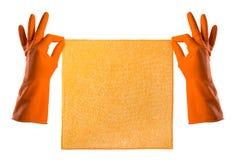 La mano in guanto di gomma arancio tiene uno straccio arancio - alloggi la pulizia Fotografie Stock Libere da Diritti