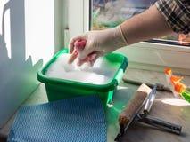 la mano in guanto schiaccia fuori lo straccio bagnato per pulire la finestra immagine stock