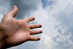La mano ha allungato ad un cielo riempito di nuvole scure adatto a copertina di libro, illustrazione della carta, presentazione immagini stock