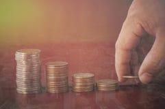 La mano ha messo i soldi sul mucchio della moneta Immagine Stock