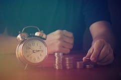 La mano ha messo i soldi sul mucchio della moneta sulla tavola Immagini Stock Libere da Diritti