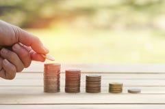 La mano ha messo i soldi sul mucchio delle monete su fondo di legno fotografie stock