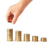 La mano ha messo la moneta alla pila dei soldi   Fotografia Stock
