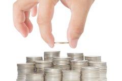 La mano ha messo la moneta di oro alla pila di monete isolate su backgroun bianco Fotografia Stock