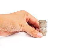 La mano ha messo la moneta a soldi Immagini Stock