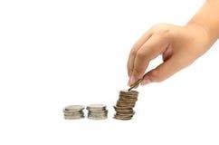 La mano ha messo le monete alla pila di monete Immagini Stock