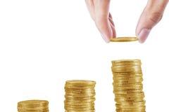 La mano ha messo le monete nella pila di monete Immagine Stock