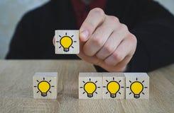 La mano ha selezionato i cubi di legno con il simbolo della lampadina della luce gialla sulla tavola di legno Nuovi idea, concett fotografia stock