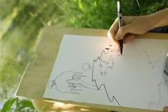 La mano hace el bosquejo del proyecto del lago de la charca en el bosque Imagen de archivo libre de regalías