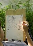 La mano hace el bosquejo del proyecto del lago de la charca en el bosque Foto de archivo