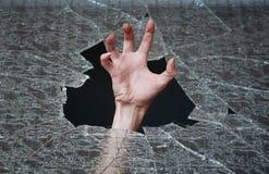 La mano hace su manera a través del vidrio quebrado Imagen de archivo libre de regalías