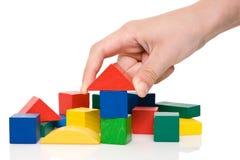 la mano hace un edificio de bloques coloreados. Imagen de archivo