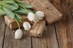 La mano hizo la caja a mano presente con las flores de los tulipanes Imagen de archivo