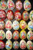 La mano hizo los huevos de Pascua a mano de madera en fondo negro Foto de archivo