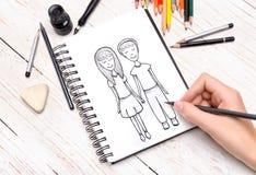 La mano humana con el lápiz dibuja en cuaderno Imagen de archivo libre de regalías