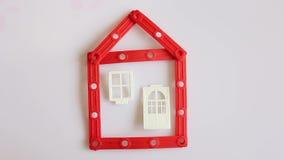 La mano humana construye la casa roja en el fondo blanco almacen de metraje de vídeo