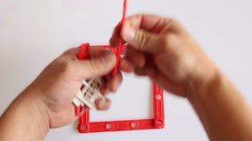 La mano humana construye la casa roja en el fondo blanco almacen de video