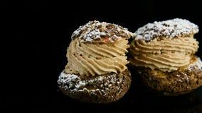 La mano humana fija el postre de los pasteles de los choux llenado de crema del caramelo en fila metrajes