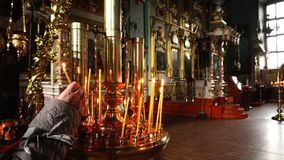La mano humana pone una vela ardiente en el templo almacen de video