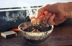 La mano humana se sostiene sobre el cigarrillo del cenicero, que está fumando pesadamente foto de archivo libre de regalías