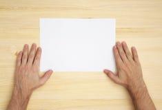 La mano humana sostiene un papel en blanco Imagenes de archivo