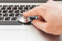 La mano inclina un estetoscopio a un teclado del ordenador portátil foto de archivo