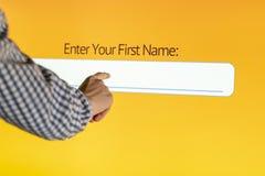 La mano incorpora el nombre en una pantalla d del panel táctil fotos de archivo