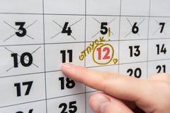 La mano indica il dito sul calendario l'ultimo giorno lavorativo prima del rilascio fotografia stock libera da diritti