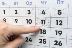 La mano indica il giorno sul calendario con la vacanza dell'iscrizione fotografia stock