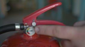La mano indica un calibro del manometro nell'estintore, fine su stock footage