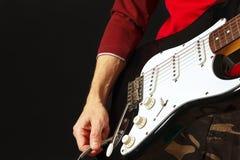 La mano inserta el conector de entrada a la guitarra eléctrica en fondo negro Imagen de archivo