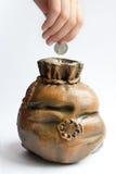 La mano inserta una moneda en la batería guarra Fotografía de archivo libre de regalías