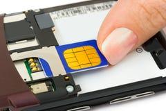 La mano instala la tarjeta del sim al teléfono móvil Foto de archivo libre de regalías