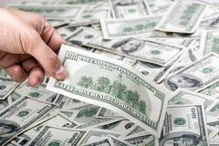Sosteniendo 100 US$ entre otros Imagen de archivo libre de regalías