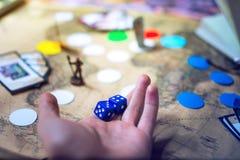 La mano lanza los dados en los juegos de mesa del mapa del mundo del fondo Fotos de archivo libres de regalías