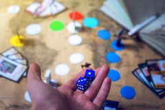 La mano lanza los dados en los juegos de mesa del mapa del mundo del fondo Foto de archivo libre de regalías