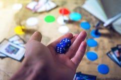 La mano lanza los dados en los juegos de mesa del mapa del mundo del fondo Fotografía de archivo libre de regalías