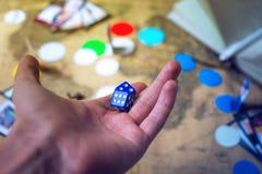 La mano lanza los dados en los juegos de mesa del mapa del mundo del fondo Imágenes de archivo libres de regalías