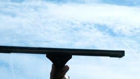 La mano limpia el limpiador con una ventana sucia del primer exterior, cámara lenta metrajes