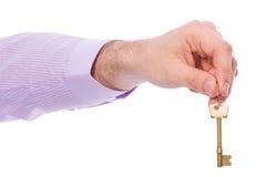 La mano lleva a cabo clave de la puerta de la casa imagenes de archivo