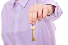 La mano lleva a cabo clave de la puerta de la casa imagen de archivo libre de regalías