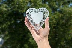 La mano lleva a cabo el corazón hecho del metal blanco en un parque delante de árboles Foto de archivo
