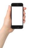 La mano lleva a cabo el espacio del iPhone 5s gris en el fondo blanco Imágenes de archivo libres de regalías