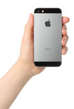 La mano lleva a cabo el espacio del iPhone 5s gris en el fondo blanco Fotografía de archivo